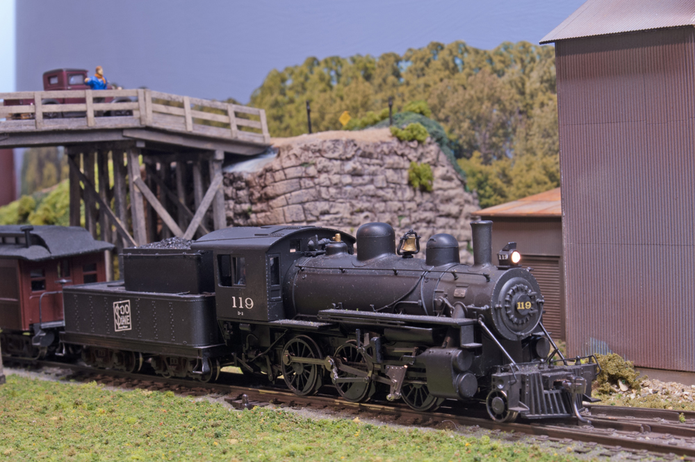 An HO scale 2-6-0 Mogul steam locomotive passes under a wooden road bridge and past a corrugated metal building.