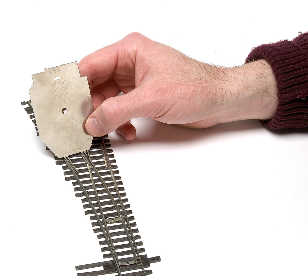Checking a turnout with a National Model Railroad Association standards gauge.