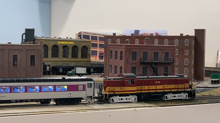 A locomotive pulls a train of Rapido 8600-series coaches around Steve Tello's HO scale model train layout.