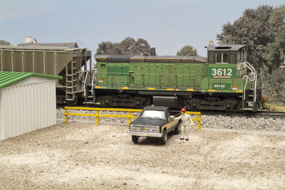 Central Valley HO scale fence painted yellow in a yard office scene with BNSF SW1000 no. 3612 and pickup truck.