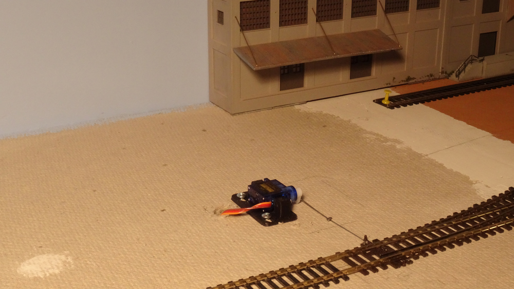 ALT: A small servo is connected by a stiff wire to the model railroad turnout it controls.