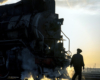 A silhouetted person in front of a steam locomotive.