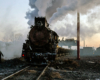 A steam locomotive pauses with a train in an industrial rail yard.