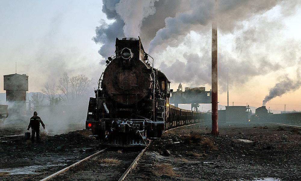 Steam locomotive paused in an industrial rail yard.