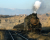 Steam locomotive hauls a train through a mined area. Snow capped mountains in background.
