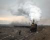 A steam locomotive hauls a train out of a rail yard in an arid desert scene.