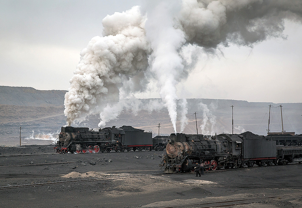 Two steam locomotives paused at the base of an open pit coal mine.