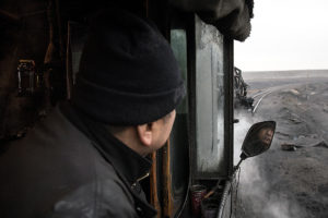 A train crewman peers out his cab window. His face is reflected in a mirror.