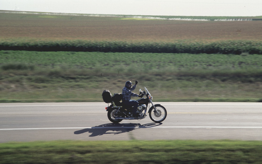 Motorcycle rider waiving while driving.