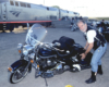 Man posing with motorcycle near a passenger train.