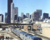 Amtrak passenger train on a bright and clear day with Chicago's skyline in the background.