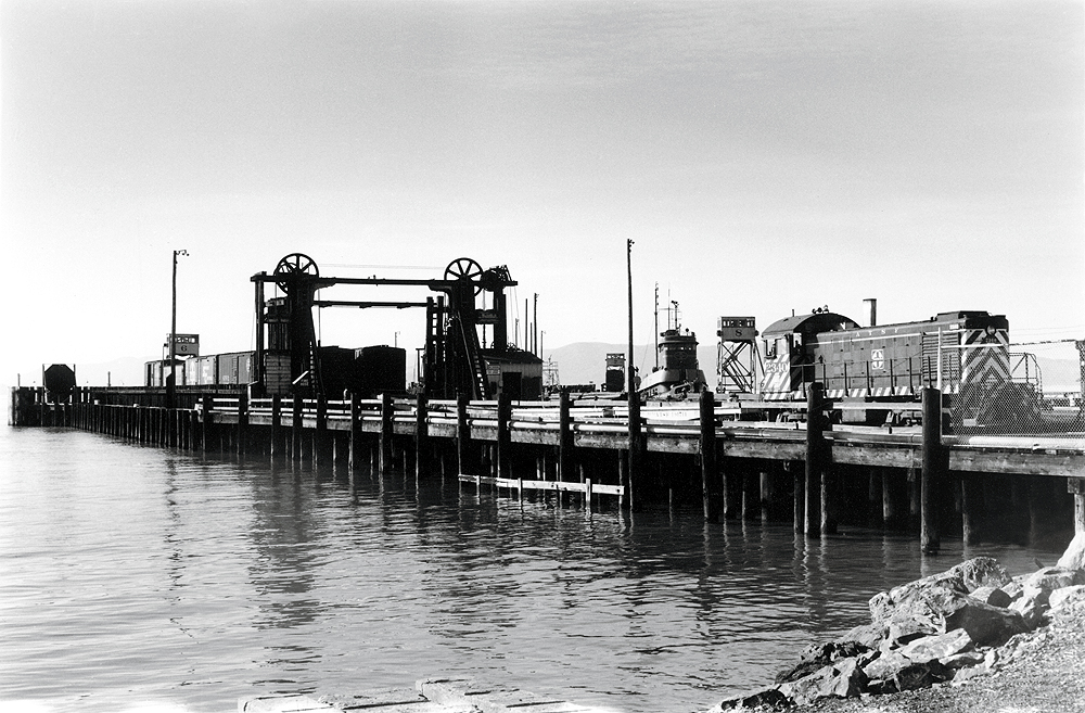Locomotive works with freight cars on a floating barge connected to land. Black and white.