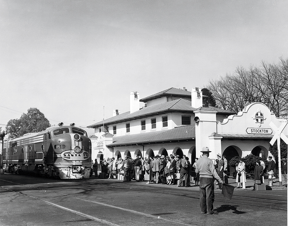 A cab unit-style locomotive in front of a train station surrounded by people. Black and white.