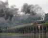 Steam locomotive leading a passenger train over a river on an old stone bridge.