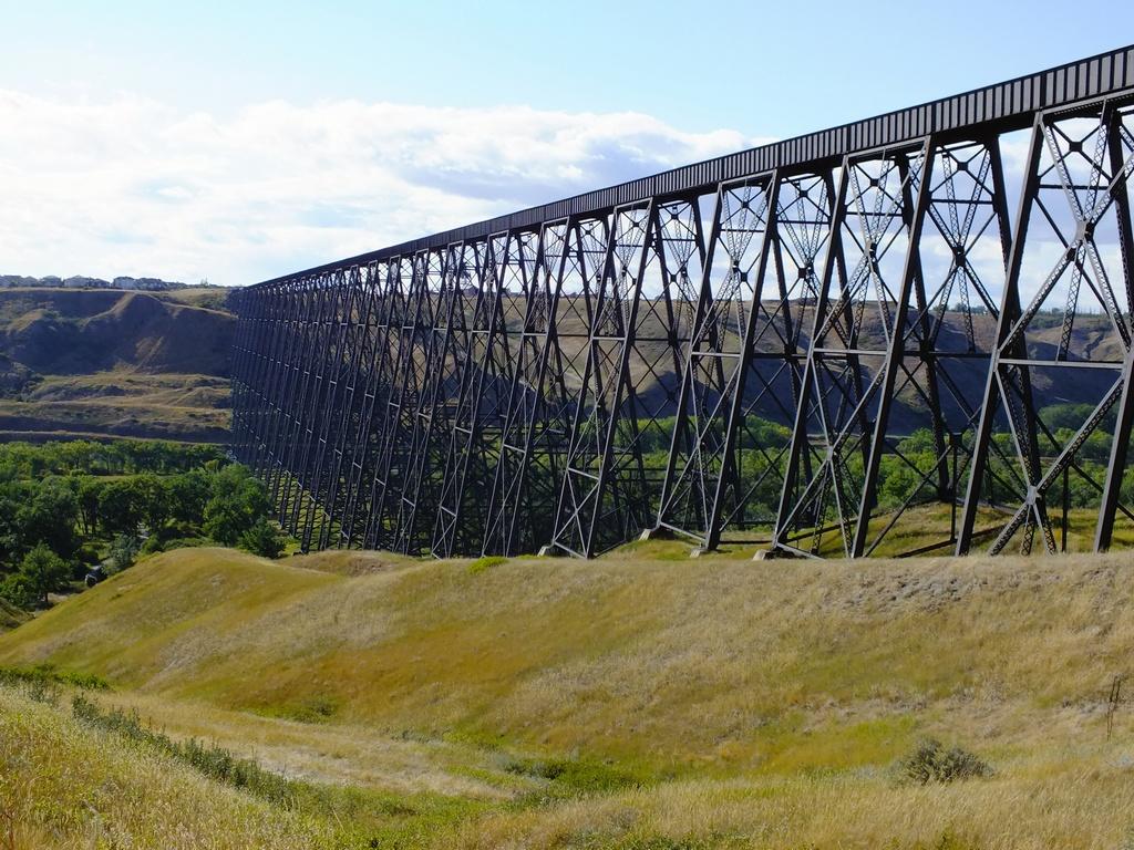 Long steel bridge in a prairie landscape.