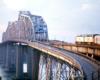 Amtrak diesel locomotives lead a passenger train over a large truss span bridge over a river.