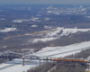 Overhead view of a train moving across a bridge above a frozen river in winter time.