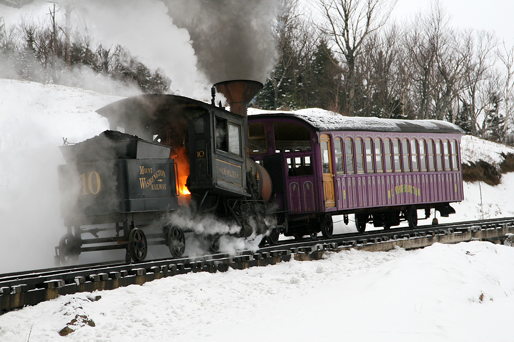 Cog steam locomotive with a passenger car on a steep incline.