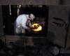 Railroad worker shovels coal lumps into a steam locomotive firebox.