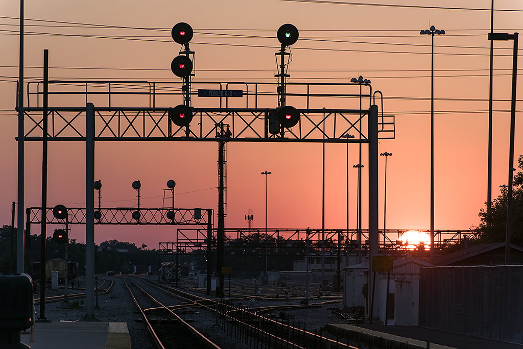 Sunset over a rail yard and signals.