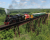 Steam locomotive hauling a mixed tourist train over a long bridge.