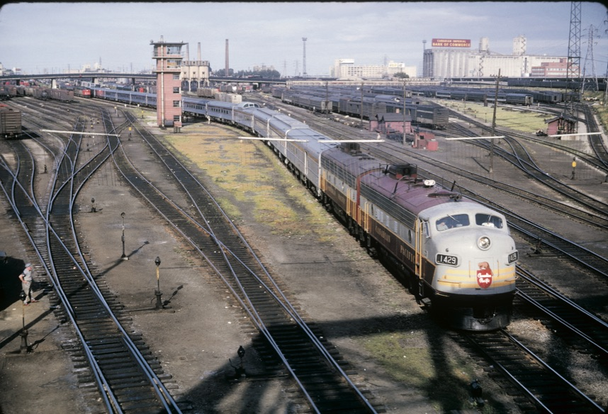 A maroon and gray diesel locomotive leads a passenger train in a rail yard.