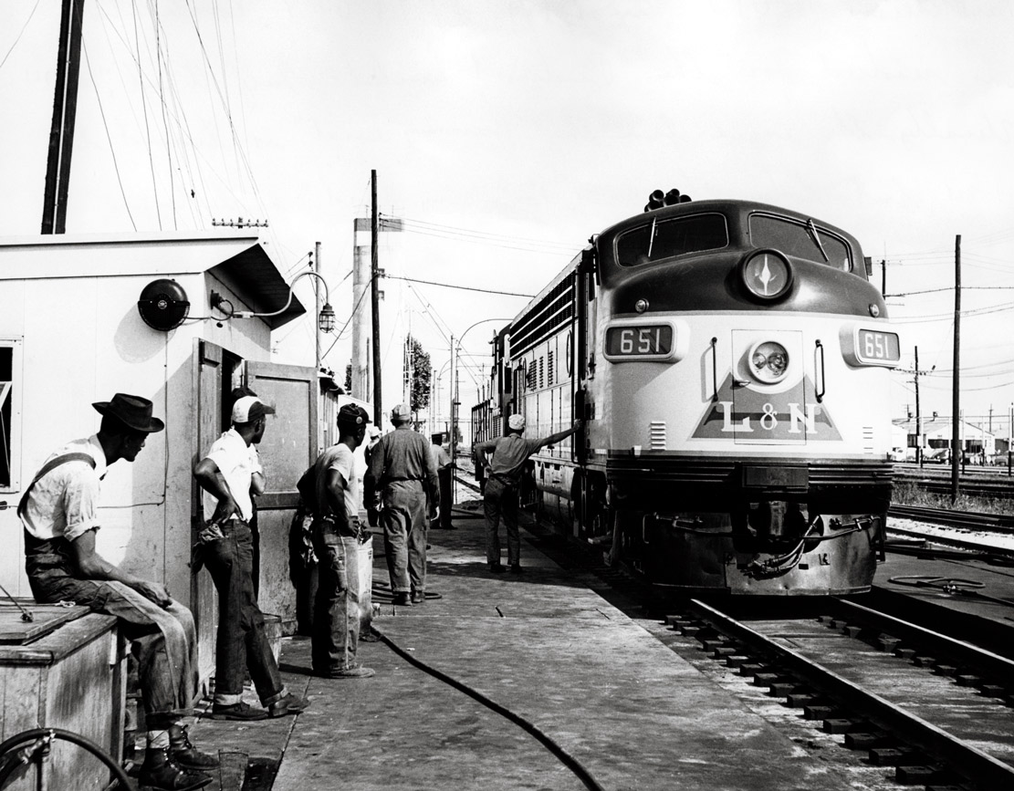 Workers with two passenger diesel locomotives