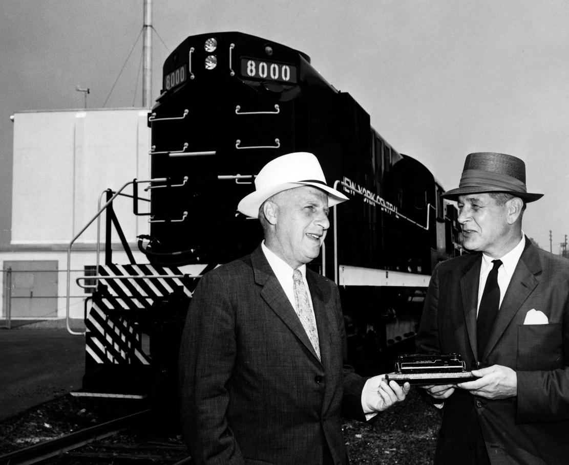 Two men in front of road-switcher diesel locomotive