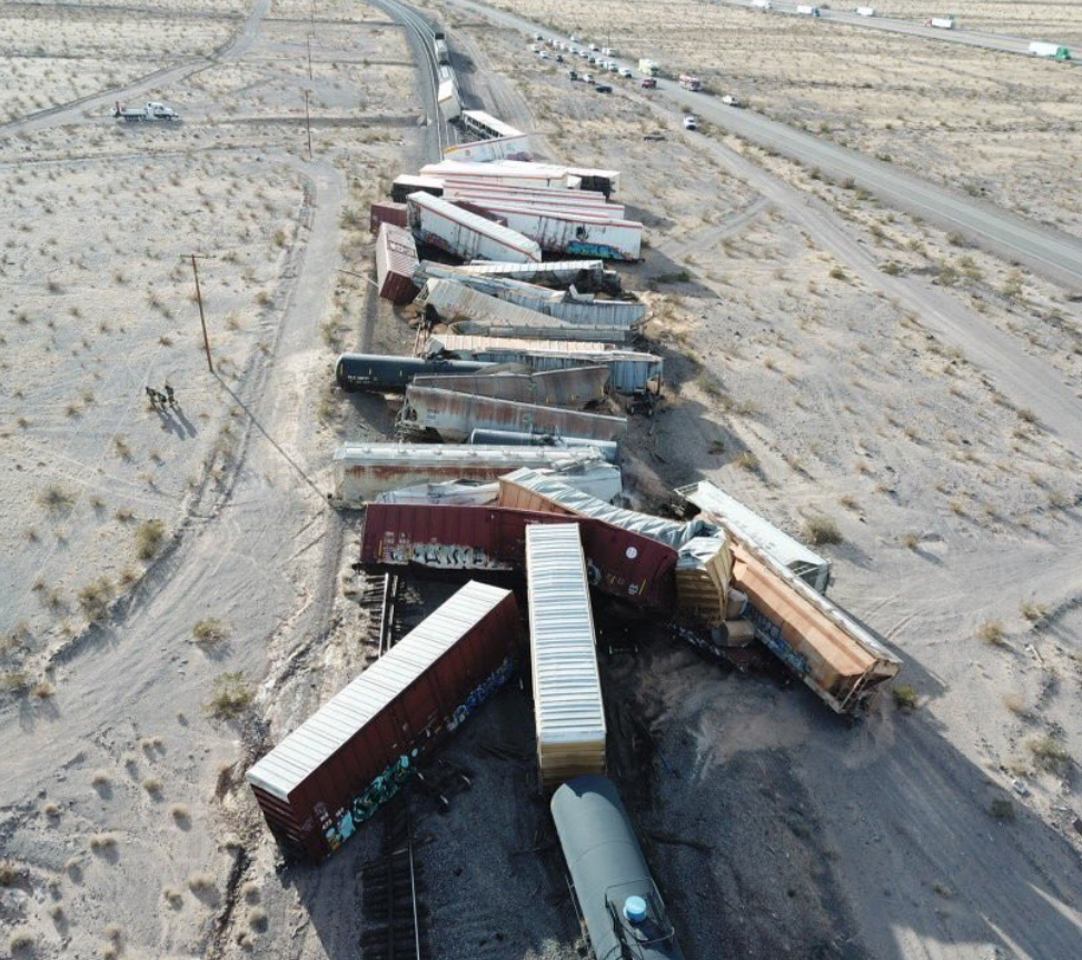 A vertical image of a train derailment in an arid landscape with low-angle sunlight.