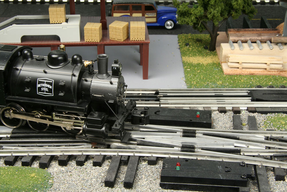 A short O gauge 0-6-0t steam switcher approaches a pair of track turnouts