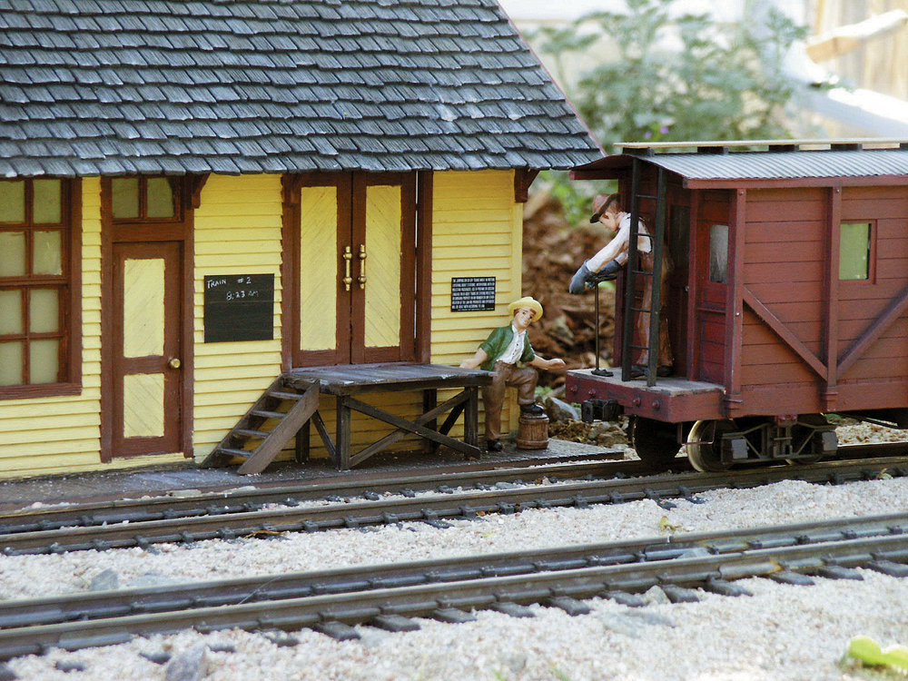 A caboose passes the station on a garden railway.