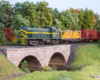 A green Alco diesel leading a freight train rolls onto a stone arch bridge over a creek