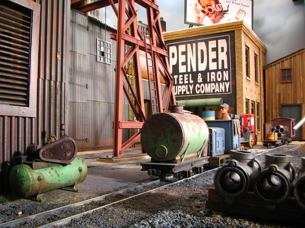 A man on a small industrial shifter moving a tank car on narrow gauge tracks is dwarfed by surrounding industrial buildings