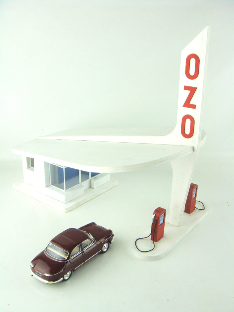 Miniature vintage gas station with car parked out by the pump