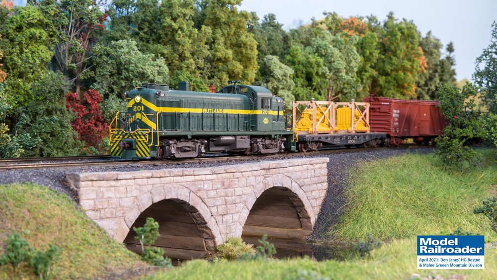 A green diesel locomotive leading a string of freight cars crosses a stone arch bridge over a creek