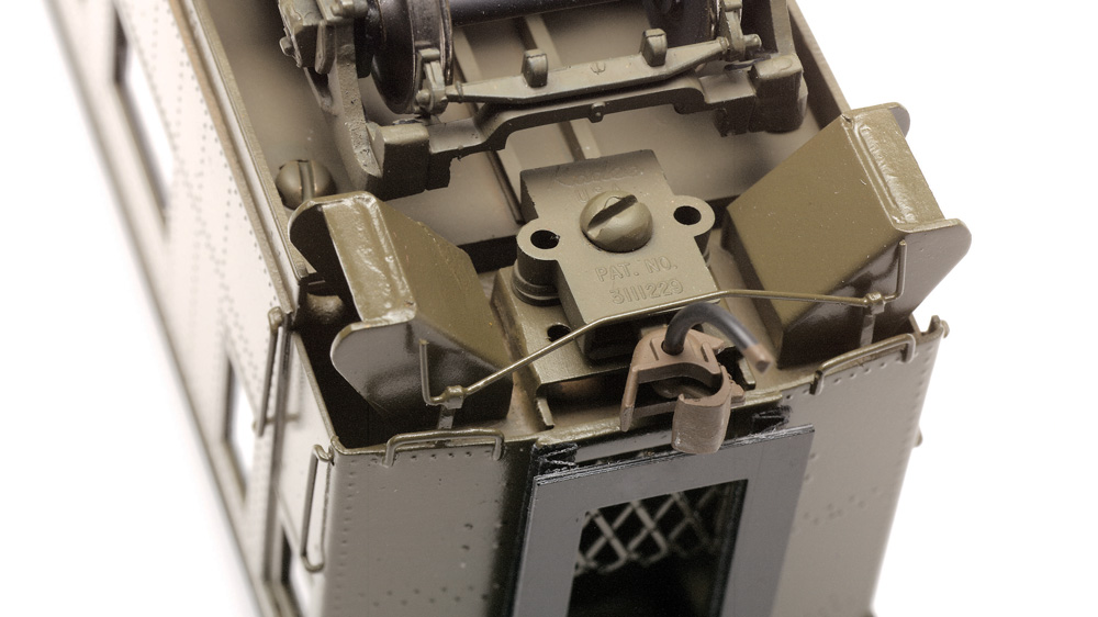 A Kadee knuckle coupler mounted on the underside of an HO scale heavyweight passenger car.