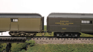 Two olive green HO scale heavyweight passenger cars are compared for height.