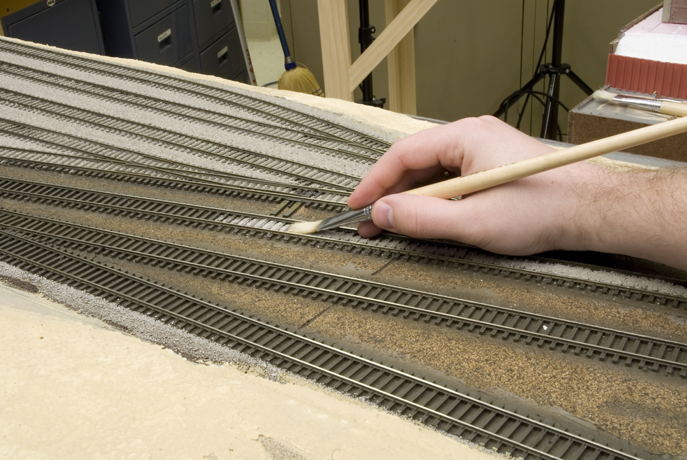 """Spreading ballast with ½""""-wide paint brush."""