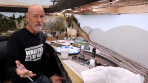 Steve Brown holding a paint brush in his hand while showing how to paint a backdrop for a model railroad