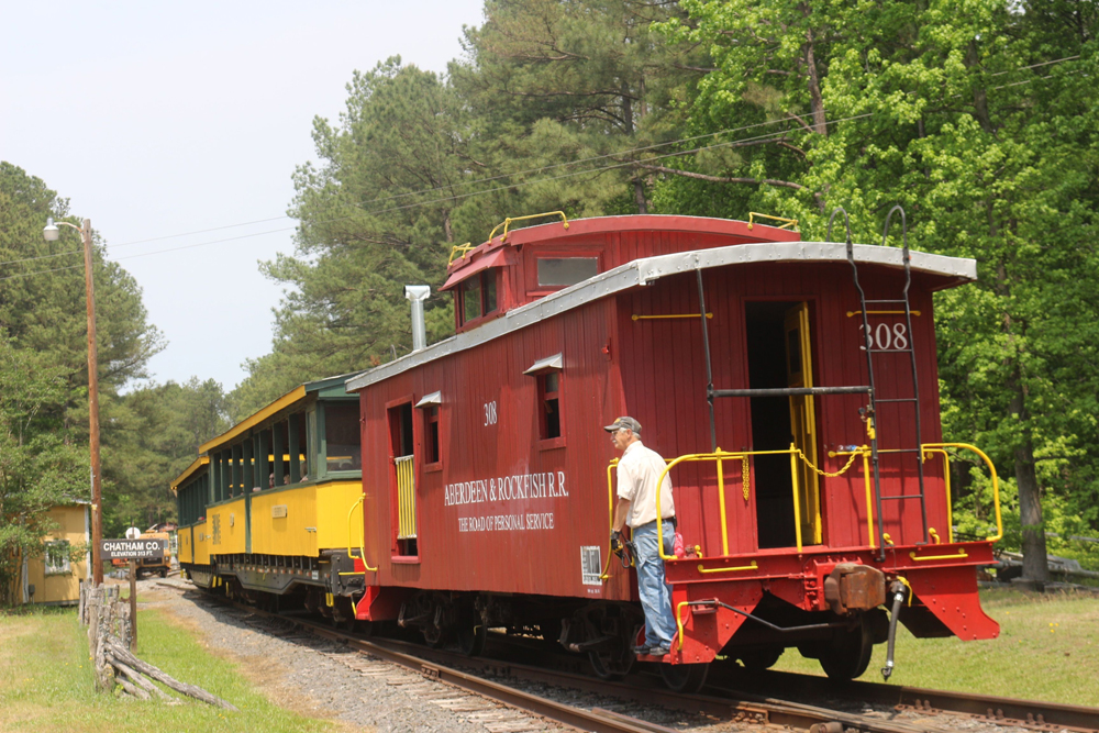A person rides the steps of a caboose on the back of a train in a green forested landscape.