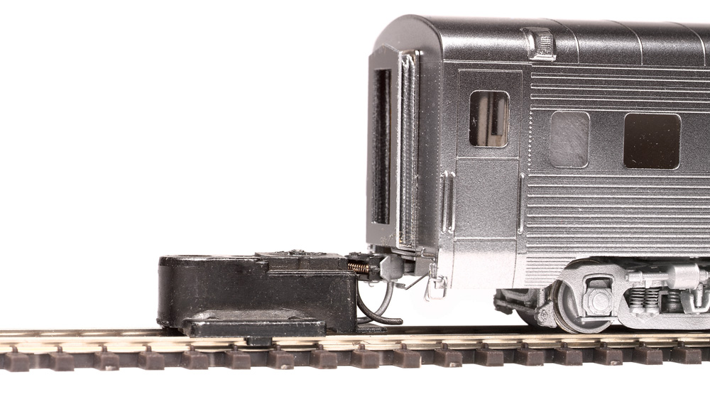 The height of a knuckle coupler on an HO scale passenger car is checked with a Kadee gauge.