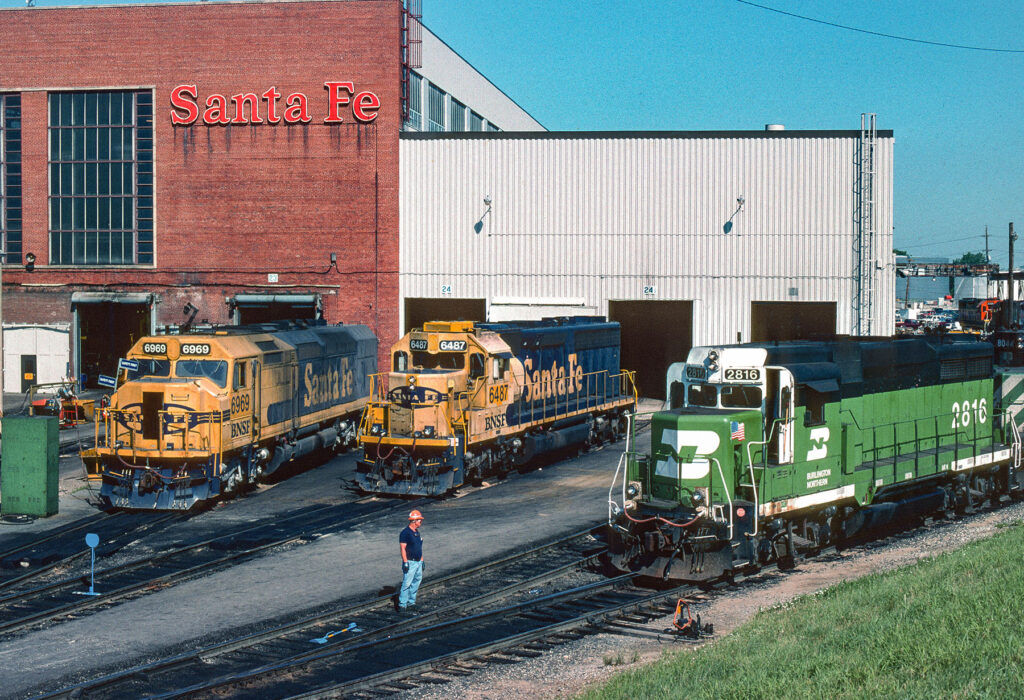 Three diesel locomotives outside shop building