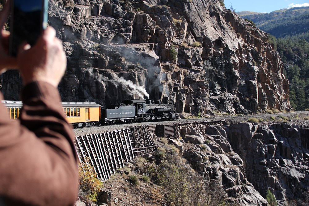 A steam locomotive-hauled passenger train navigating a rocky slope as seen from a car in the rear of the train.