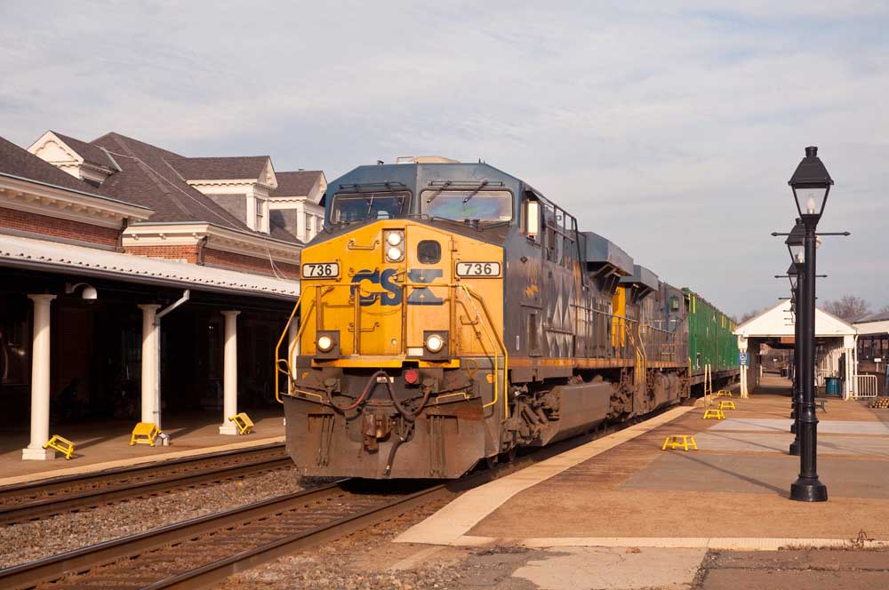 Yellow and blue diesel powers freight train past brick station