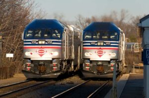 Two blue and silver commuter trains pass in station