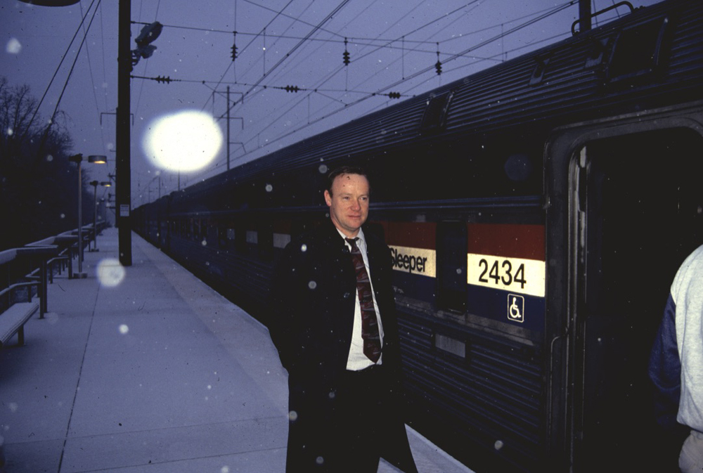 Attendant on platform outside train at night in snow