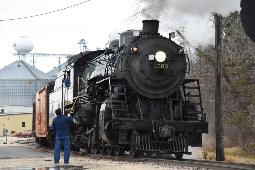 A worker holds a pole next to a steam locomotive moving slowly.