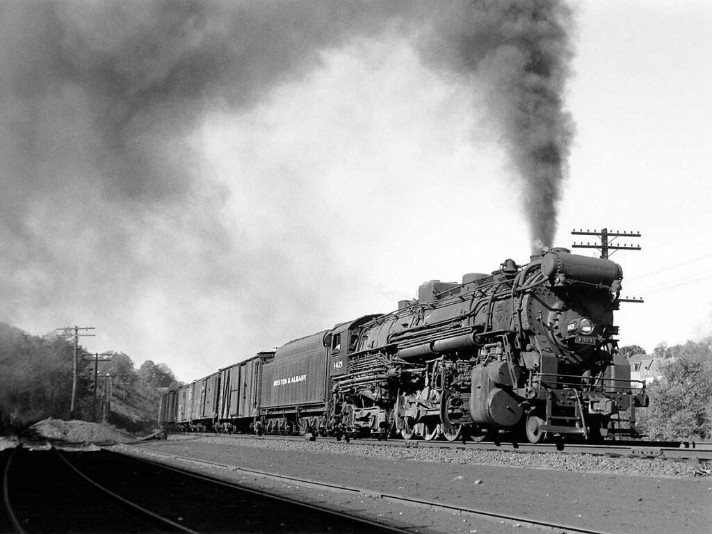 Steam locomotive produces smoke on fast train