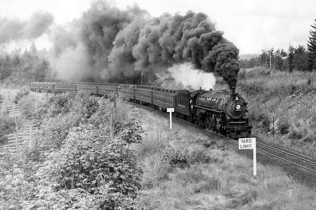 Steam locomotive smoking with passenger train on curve