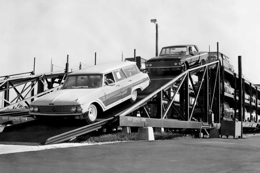 New automobiles are driven down a ramp off a railroad car